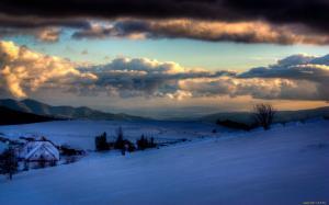 белый снег лежит под темными тучами на закате