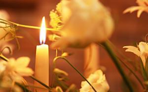 свеча горит среди цветов